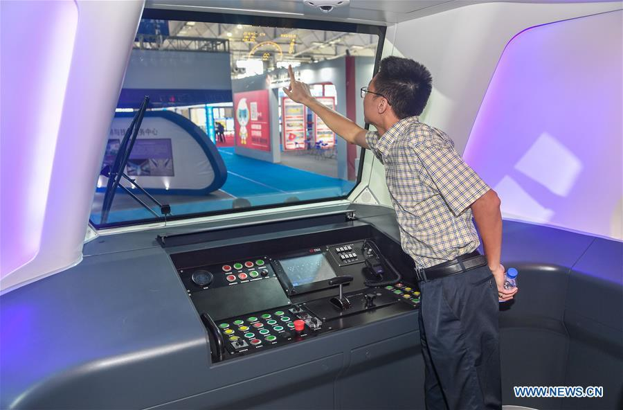 A man visits the cockpit of a new-generation carbon-fiber light rail train at an exhibition held in Changchun, capital of northeast China\'s Jilin Province, Sept. 7, 2018. The body of the train is made of carbon fiber composite, making it more energy-efficient, according to its manufacturer CRRC Changchun Railway Vehicles Co., Ltd. (Xinhua/Xu Chang)