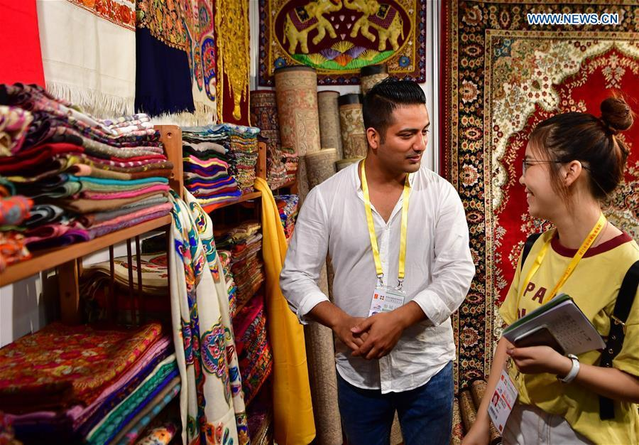 An exhibitor from India introduces scarfs to a visitor at the 20th China International Fair for Investment and Trade in Xiamen, southeast China\'s Fujian Province, Sept. 8, 2018. (Xinhua/Wei Peiquan)
