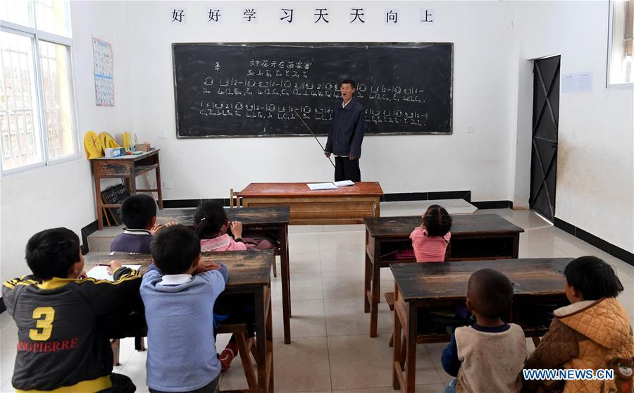 Wang Zhengxiang teaches music to students at Ayiyang Primary School in Sanmeng Village of Luquan Yi and Miao Autonomous County, southwest China\'s Yunnan Province, Sept. 6, 2018. One teacher, eight students, none was and will be given up thanks to rural teacher Wang Zhengxiang. Wang Zhengxiang of Miao ethnic group, 56, is the only teacher and has been teaching at the remote village primary school of Ayiyang for 38 years. Ayiyang Primary School, lying at an altitude of 2,600 meters above sea level and surrounded by mountains, is not within easy reach of outside world. There are just eight students at the school. Yet Wang takes care of his students with love, consideration and strong sense of responsibility. He buys shoes and daily goods for poverty-stricken students with his own money, and he has tried every means to keep those who wanted to drop out due to economic insufficiency. \