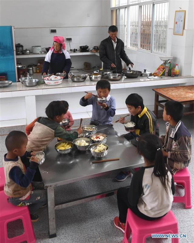 Wang Zhengxiang (R, back) and his wife prepare meals for the students at Ayiyang Primary School in Sanmeng Village of Luquan Yi and Miao Autonomous County, southwest China\'s Yunnan Province, Sept. 6, 2018. One teacher, eight students, none was and will be given up thanks to rural teacher Wang Zhengxiang. Wang Zhengxiang of Miao ethnic group, 56, is the only teacher and has been teaching at the remote village primary school of Ayiyang for 38 years. Ayiyang Primary School, lying at an altitude of 2,600 meters above sea level and surrounded by mountains, is not within easy reach of outside world. There are just eight students at the school. Yet Wang takes care of his students with love, consideration and strong sense of responsibility. He buys shoes and daily goods for poverty-stricken students with his own money, and he has tried every means to keep those who wanted to drop out due to economic insufficiency. \