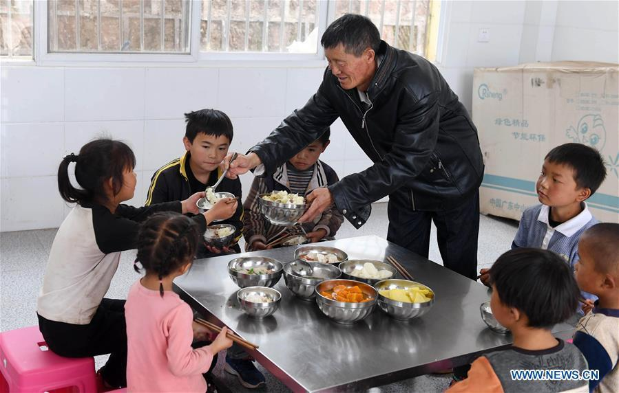 Wang Zhengxiang prepares meals for students at Ayiyang Primary School in Sanmeng Village of Luquan Yi and Miao Autonomous County, southwest China\'s Yunnan Province, Sept. 6, 2018. One teacher, eight students, none was and will be given up thanks to rural teacher Wang Zhengxiang. Wang Zhengxiang of Miao ethnic group, 56, is the only teacher and has been teaching at the remote village primary school of Ayiyang for 38 years. Ayiyang Primary School, lying at an altitude of 2,600 meters above sea level and surrounded by mountains, is not within easy reach of outside world. There are just eight students at the school. Yet Wang takes care of his students with love, consideration and strong sense of responsibility. He buys shoes and daily goods for poverty-stricken students with his own money, and he has tried every means to keep those who wanted to drop out due to economic insufficiency. \