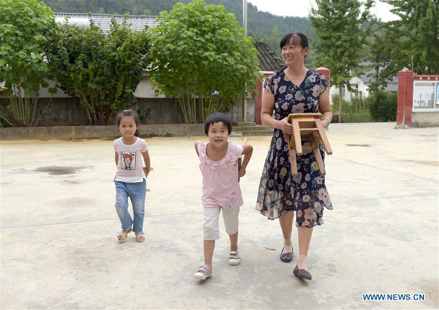 Jiang Xiulan prepares a game with students between classes in Qingxi Central Primary School in Chaerlong village, Wushi town, Huangshan City of east China\'s Anhui Province, Sept. 7, 2018. Since 1983 when she began her career as a teacher, Jiang has been working in the \