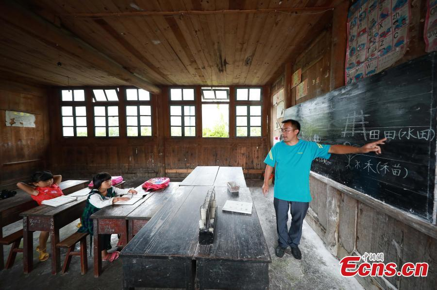 Yang Changjun teaches Chinese to Wang Fangying (C), a first grader, while his daughter, 6, also sits in the classroom at a school in Danggan Village, Paitiao Town, Guizhou Province, Sept. 7, 2018. Yang, 40, is the only teacher in the school that has one first grader and seven pre-school children from nearby villages. If not for the school, children would have to travel to a town more than 20 kilometers away to study. (Photo: China News Service/Huang Xiaohai)