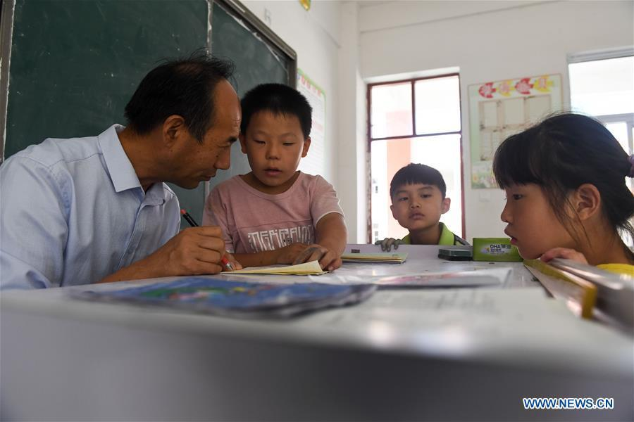 With help of students, Guo Yue corrects students\' papers in Guozhai Primary School, Taihe County of east China\'s Anhui Province, Sept. 7, 2018. Guo, suffering a chronic loss of eyesight due to an illness a few years after he began his career as teacher in 1986, managed to keep teaching in the school. Almost totally blind, Guo also teaches in music and ethical education classes in addition to Chinese. (Xinhua/Zhang Duan)