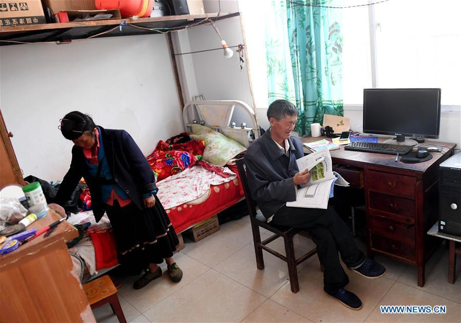 Wang Zhengxiang and his wife Pan Xiuhua are seen at the dormitory of Ayiyang Primary School in Sanmeng Village of Luquan Yi and Miao Autonomous County, southwest China\'s Yunnan Province, Sept. 5, 2018. One teacher, eight students, none was and will be given up thanks to rural teacher Wang Zhengxiang. Wang Zhengxiang of Miao ethnic group, 56, is the only teacher and has been teaching at the remote village primary school of Ayiyang for 38 years. Ayiyang Primary School, lying at an altitude of 2,600 meters above sea level and surrounded by mountains, is not within easy reach of outside world. There are just eight students at the school. Yet Wang takes care of his students with love, consideration and strong sense of responsibility. He buys shoes and daily goods for poverty-stricken students with his own money, and he has tried every means to keep those who wanted to drop out due to economic insufficiency. \