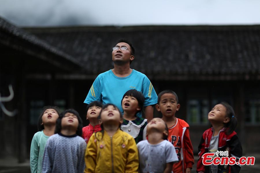 Yang Changjun leads children in the flag-raising ceremony at a school in Danggan Village, Paitiao Town, Guizhou Province, Sept. 7, 2018. Yang, 40, is the only teacher in the school that has one first grader and seven pre-school children from nearby villages. If not for the school, children would have to travel to a town more than 20 kilometers away to study. (Photo: China News Service/Huang Xiaohai)
