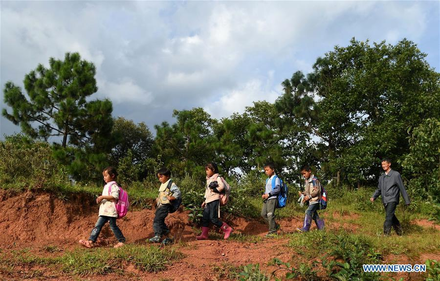 Wang Zhengxiang (1st R) sends students back home after school in Sanmeng Village of Luquan Yi and Miao Autonomous County, southwest China\'s Yunnan Province, Sept. 5, 2018. One teacher, eight students, none was and will be given up thanks to rural teacher Wang Zhengxiang. Wang Zhengxiang of Miao ethnic group, 56, is the only teacher and has been teaching at the remote village primary school of Ayiyang for 38 years. Ayiyang Primary School, lying at an altitude of 2,600 meters above sea level and surrounded by mountains, is not within easy reach of outside world. There are just eight students at the school. Yet Wang takes care of his students with love, consideration and strong sense of responsibility. He buys shoes and daily goods for poverty-stricken students with his own money, and he has tried every means to keep those who wanted to drop out due to economic insufficiency. \