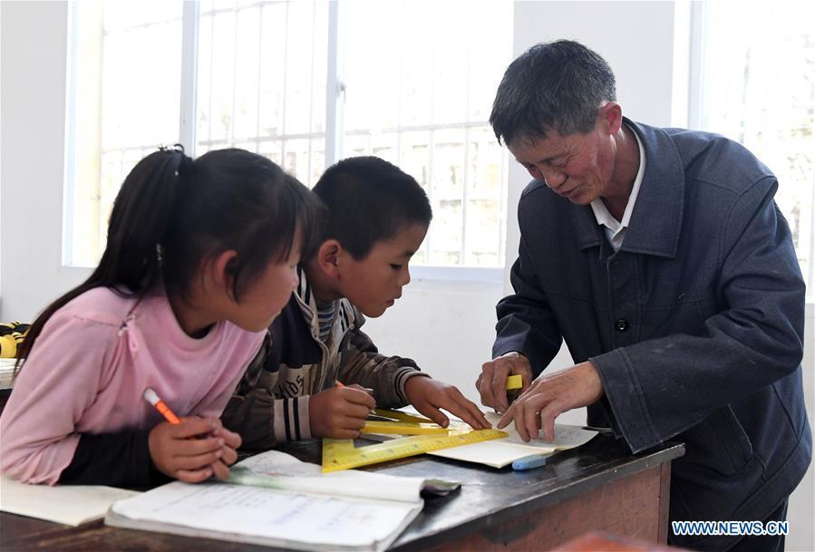 Wang Zhengxiang (1st R) teaches students at Ayiyang Primary School in Sanmeng Village of Luquan Yi and Miao Autonomous County, southwest China\'s Yunnan Province, Sept. 5, 2018. One teacher, eight students, none was and will be given up thanks to rural teacher Wang Zhengxiang. Wang of Miao ethnic group, 56, is the only teacher and has been teaching at the remote village primary school of Ayiyang for 38 years. Ayiyang Primary School, lying at an altitude of 2,600 meters above sea level and surrounded by mountains, is not within easy reach of outside world. There are just eight students at the school. Yet Wang takes care of his students with love, consideration and strong sense of responsibility. He buys shoes and daily goods for poverty-stricken students with his own money, and he has tried every means to keep those who wanted to drop out due to economic insufficiency. \
