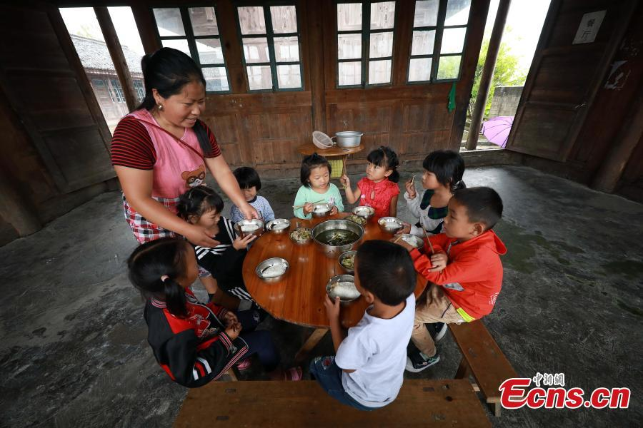 Teacher Yang Changjun's wife Li Li prepares lunch for children at a school in Danggan Village, Paitiao Town, Guizhou Province, Sept. 7, 2018. Yang, 40, is the only teacher in the school that has one first grader and seven pre-school children from nearby villages. If not for the school, children would have to travel to a town more than 20 kilometers away to study. (Photo: China News Service/Huang Xiaohai)