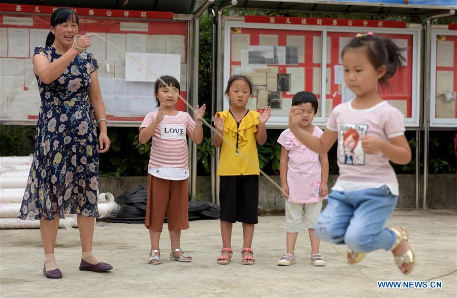 Jiang Xiulan participates in a PE class in Qingxi Central Primary School in Chaerlong village, Wushi town, Huangshan City of east China\'s Anhui Province, Sept. 7, 2018. Since 1983 when she began her career as a teacher, Jiang has been working in the \
