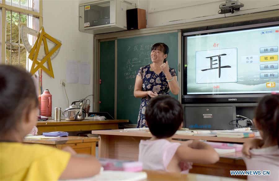 Jiang Xiulan, 53, explains the meaning of a Chinese character as she teaches in a class of Qingxi Central Primary School in Chaerlong village, Wushi town, Huangshan City of east China\'s Anhui Province, Sept. 7, 2018. Since 1983 when she began her career as a teacher, Jiang has been working in the \