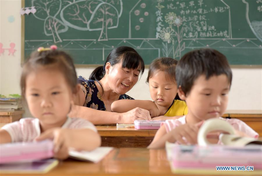 Jiang Xiulan explains as her students study in a class in Qingxi Central Primary School in Chaerlong village, Wushi town, Huangshan City of east China\'s Anhui Province, Sept. 7, 2018. Since 1983 when she began her career as a teacher, Jiang has been working in the \