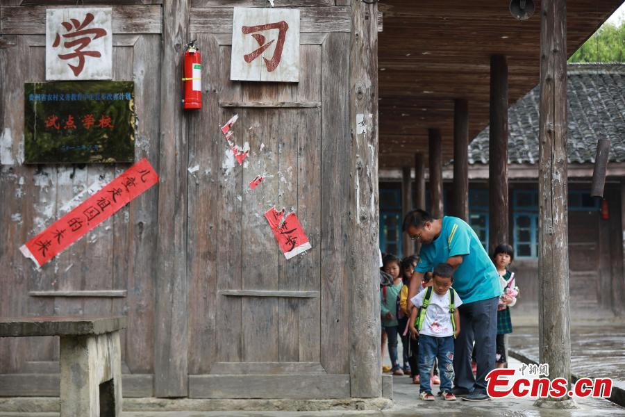 Teacher Yang Changjun sees off students as they leave school in Danggan Village, Paitiao Town, Guizhou Province, Sept. 7, 2018. Yang, 40, is the only teacher in the school that has one first grader and seven pre-school children from nearby villages. If not for the school, children would have to travel to a town more than 20 kilometers away to study. (Photo: China News Service/Huang Xiaohai)