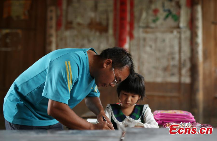 Teacher Yang Changjun instructs Wang Fangying, a first grader, in writing at a school in Danggan Village, Paitiao Town, Guizhou Province, Sept. 7, 2018. Yang, 40, is the only teacher in the school that has one first grader and seven pre-school children from nearby villages. If not for the school, children would have to travel to a town more than 20 kilometers away to study. (Photo: China News Service/Huang Xiaohai)