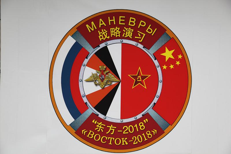 The logo of the \'Vostok-2018\' strategic drills. The drills are said to be the largest military exercises in over three decades. (Photo by PAN Mengqi/chinadaily.com.cn)  In the strategic drills, the PLA and Russian armed forces have formed a joint operational commanding system, under which military forces from the two countries will hold joint exercises including mechanized defense,fire strike and counter-attack training.