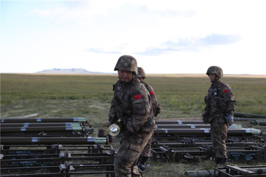 """Chinese soldiers are loading rockets into the launcher at the Tsugol training range in Russia\'s Trans-Baikal region. (Photo by PAN Mengqi/chinadaily.com.cn)  Russian Defense Minister Sergei Shoigu said earlier that the drills involve nearly 300,000 Russian troops, about 36,000 military vehicles, more than 1,000 aircraft and around 80 ships.  Shoigu said the drills """"will be unprecedented in terms of geographic scope and the strength of command and control centers and forces due to participate""""."""