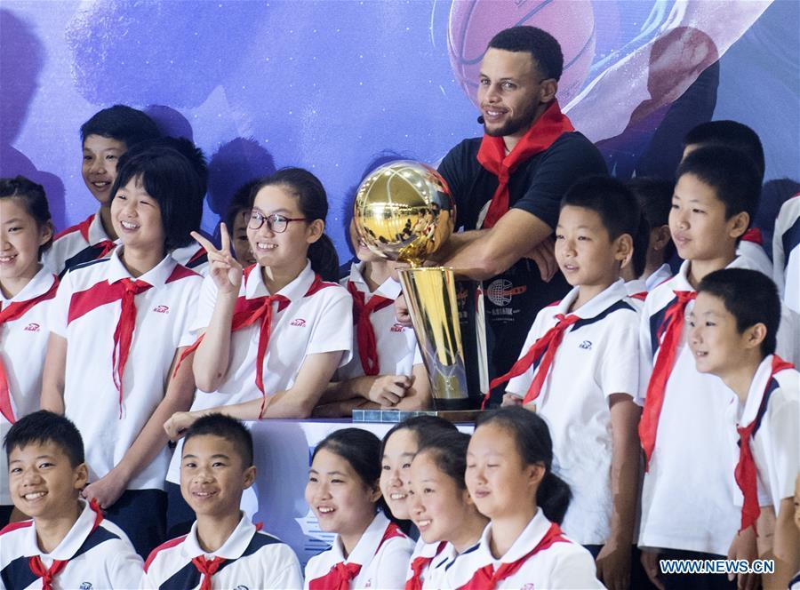 NBA player Stephen Curry of Golden State Warriors poses for photos with young players of Middle School Attached to HUST (Huazhong University of Science and Technology) during his China Tour in Wuhan, central China\'s Hubei Province, Sept. 10, 2018. (Xinhua/Xiao Yijiu)