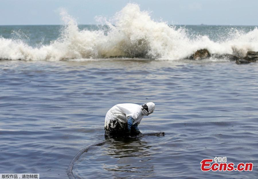 A member of the Sri Lankan coast guard removes oil from a beach after an oil spill in Uswetakeiyawa, Sri Lanka, Sept. 10, 2018. (Photo/Agencies)