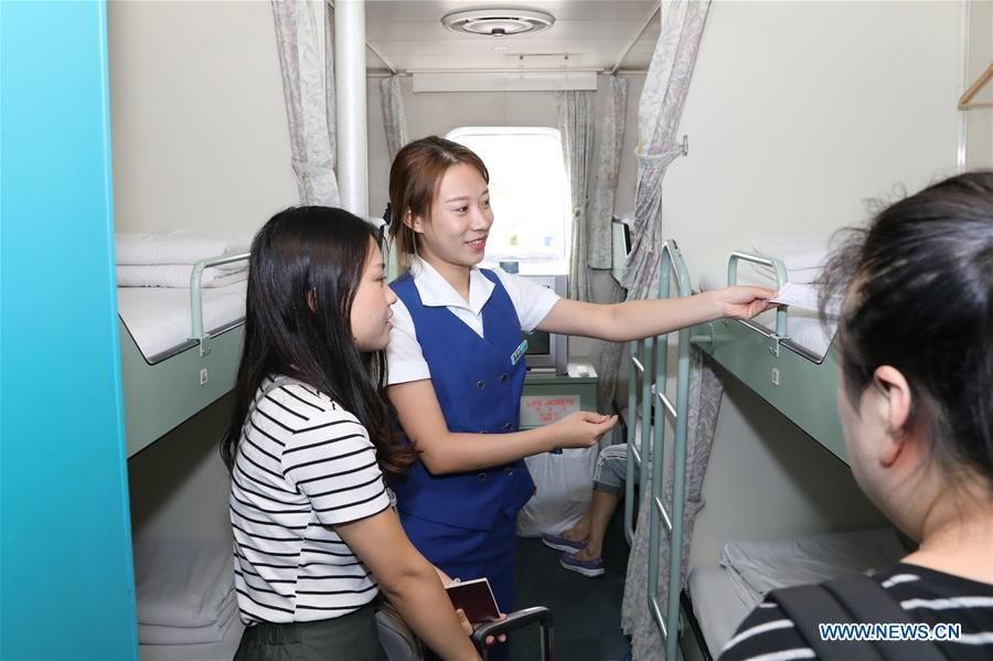 A staff member helps Chinese passengers to settle on the ferry \