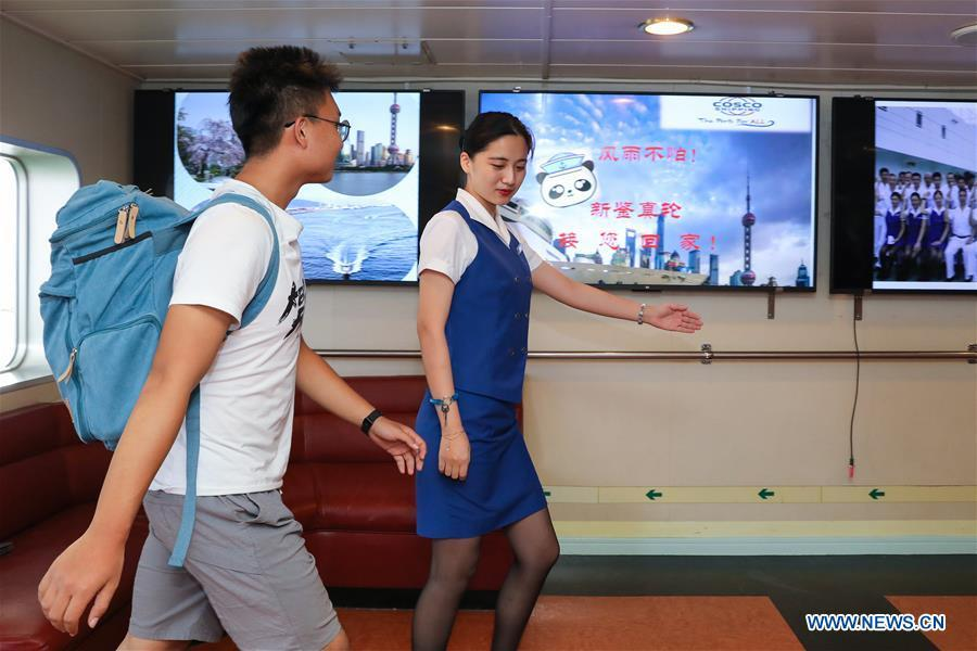 A staff member helps a Chinese passenger to board the ferry \
