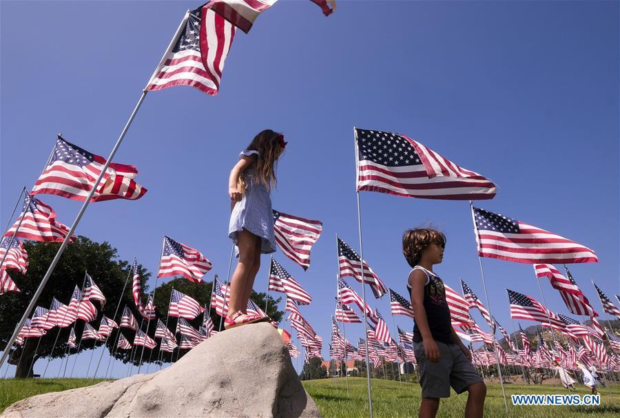 Children play among U.S. national flags erected to honor the victims of the September 11, 2001 attacks in New York, at the campus of Pepperdine University in Malibu, the United States, Sept. 10, 2018. (Photo/Xinhua)