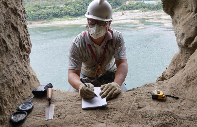 An archaeological worker writes down data about a rock tomb in Yangpitan, Yunxi county, Central China\'s Hubei Province. (Photo by Zhang Jianbo for chinadaily.com.cn)