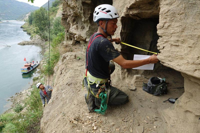 An archaeological worker measures the width of the opening of a rock tomb in Yangpitan, Yunxi county, Central China\'s Hubei Province. (Photo by Zhang Jianbo for chinadaily.com.cn)