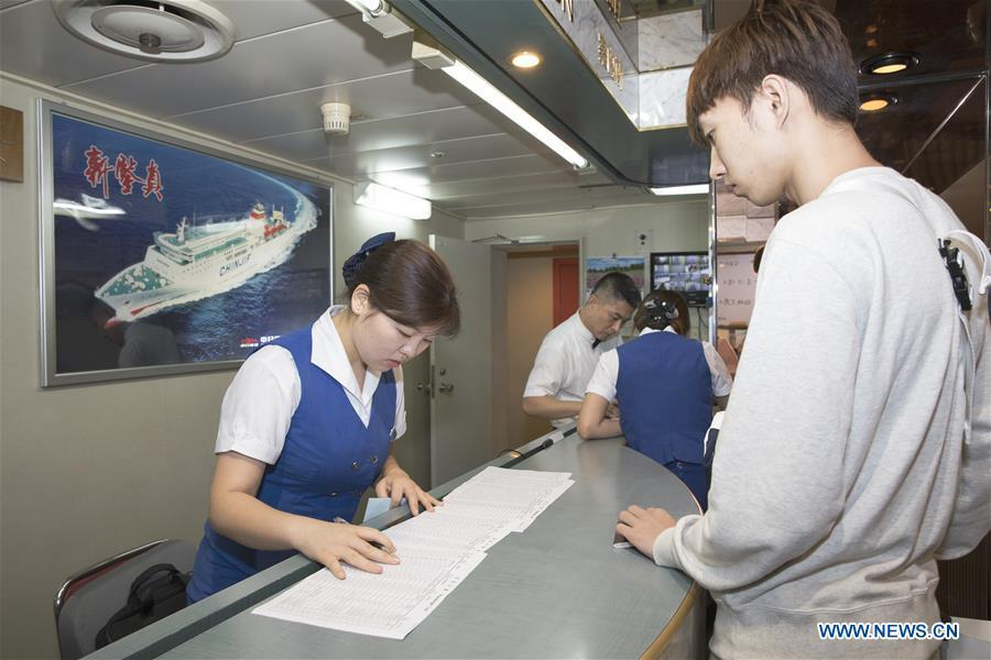 A Chinese passenger goes through boarding procedure on the ferry \