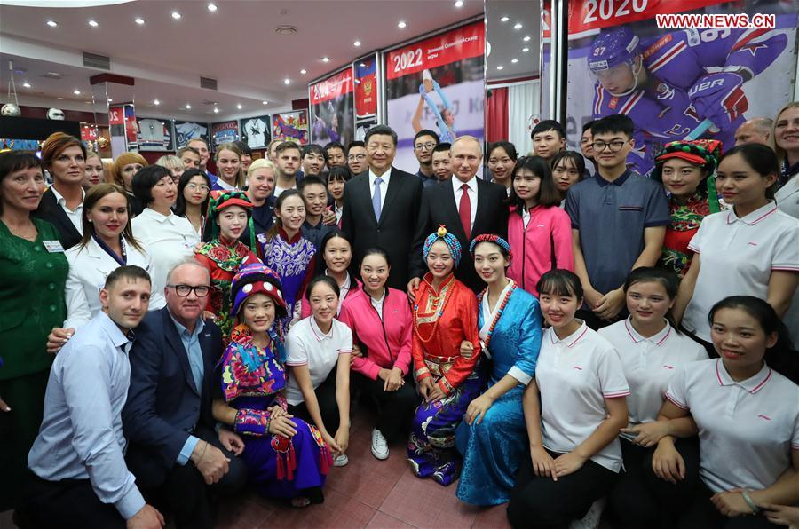 Chinese President Xi Jinping and Russian President Vladimir Putin pose for photos with youths from China and Russia and faculty representatives as they visit the All-Russian Children\'s Center \