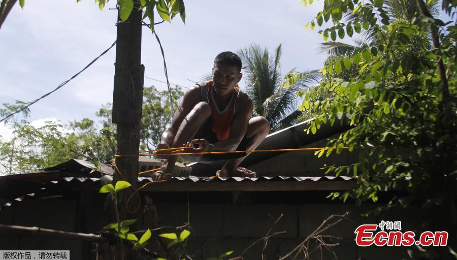 A resident secures the roof of his house in preparation for Super Typhoon Mangkut in Candon City, Ilocos Sur province, north of Manila on Sept. 13, 2018. The most powerful typhoon of the year roared toward the Philippines on Thursday, prompting thousands to evacuate ahead of its heavy rains and fierce winds that are set to strike at the weekend. (Photo/Agencies)