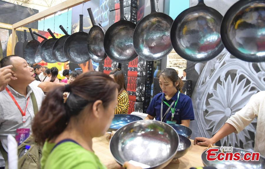 Visitors choose Zhangqiu Iron Pan at the fifth China Intangible Cultural Heritage Expo in Jinan City, Shandong Province, Sept. 13, 2018. The expo was jointly organized by the Ministry of Culture and Tourism and the Shandong provincial government. More than 200 practitioners of traditional arts and craftsmanship will showcase their skills at the expo, which will include stilt-walking, embroidery by the Qiang people and straw-weaving craftworks. (Photo: China News Service/Zhang Yong)