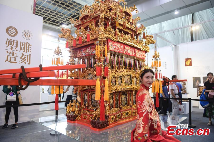 A woman wearing traditional wedding clothes poses for photo before a Ningbo Wedding Sedan Chair at the fifth China Intangible Cultural Heritage Expo in Jinan City, Shandong Province, Sept. 13, 2018. The expo was jointly organized by the Ministry of Culture and Tourism and the Shandong provincial government. More than 200 practitioners of traditional arts and craftsmanship will showcase their skills at the expo, which will include stilt-walking, embroidery by the Qiang people and straw-weaving craftworks. (Photo: China News Service/Zhang Yong)