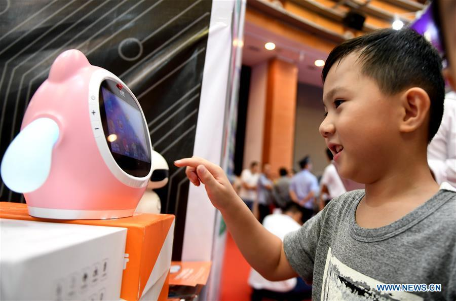 A boy interacts with a robot at the 15th China-ASEAN Expo in Nanning City, south China\'s Guangxi Zhuang Autonomous Region, Sept. 13, 2018. High-tech exhibits attracted many visitors at the expo. (Xinhua/Zhang Ailin)