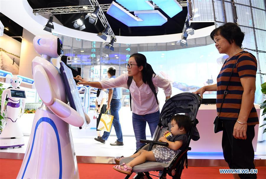 Visitors interact with a robot at the 15th China-ASEAN Expo in Nanning City, south China\'s Guangxi Zhuang Autonomous Region, Sept. 13, 2018. High-tech exhibits attracted many visitors at the expo. (Xinhua/Lu Bo\'an)