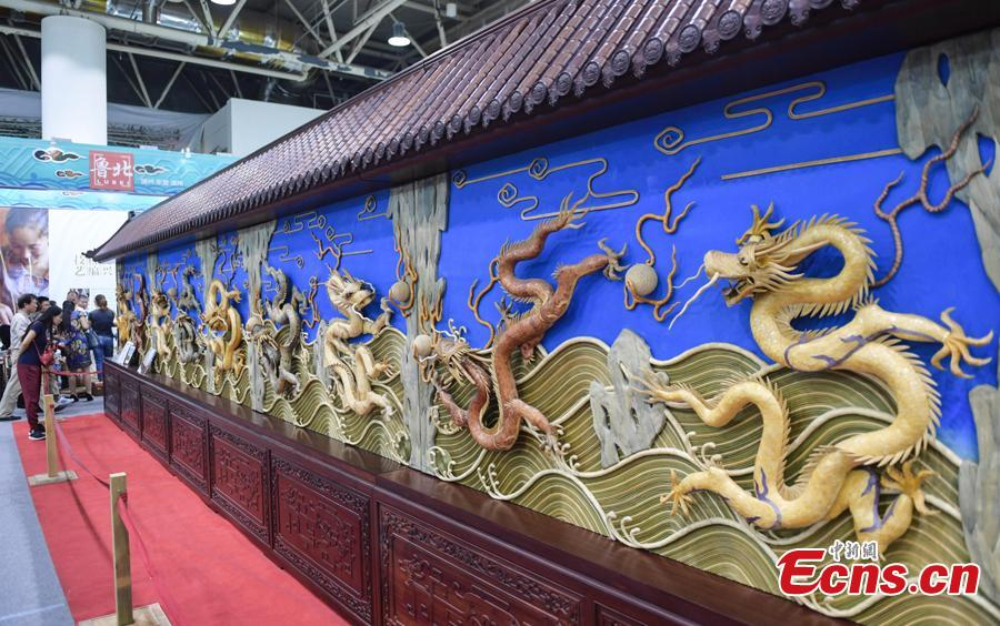 Visitors are attracted by the Nine-Dragon-Wall at the fifth China Intangible Cultural Heritage Expo in Jinan City, Shandong Province, Sept. 13, 2018. The expo was jointly organized by the Ministry of Culture and Tourism and the Shandong provincial government. More than 200 practitioners of traditional arts and craftsmanship will showcase their skills at the expo, which will include stilt-walking, embroidery by the Qiang people and straw-weaving craftworks. (Photo: China News Service/Zhang Yong)
