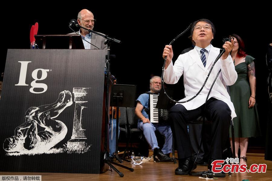 Akira Horiuchi, right of Japan, who won the Ig Nobel in medical education demonstrates his self colonoscopy technic during award ceremonies at Harvard University in Cambridge, Mass., Thursday, Sept. 13, 2018. The annual prize series honors 10 comical but practical scientific studies \