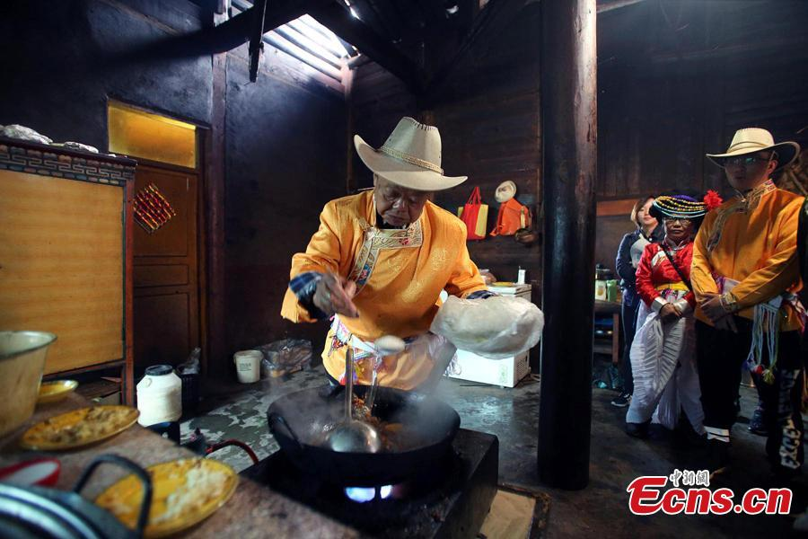 Sichuan cuisine master Fu Zuming (L) teaches cooking skills to a woman in a family of Mosuo people next to Lugu Lake in Yanyuan County, Southwest China's Sichuan Province, Sept. 13, 2018. Fu started learning to cook Sichuan food in his teens. During his visit to the Mosuo family, he combined the local specialties with Sichuan cuisine techniques to make a new dish. (Photo: China News Service/Wang Lei)