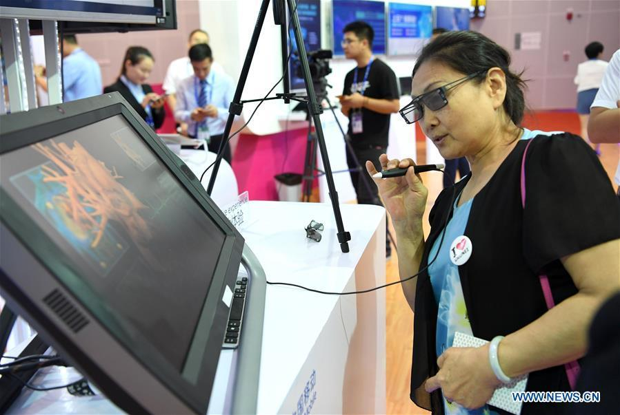 A visitor experiences a remote medical system at the 15th China-ASEAN Expo in Nanning City, south China\'s Guangxi Zhuang Autonomous Region, Sept. 13, 2018. High-tech exhibits attracted many visitors at the expo. (Xinhua/Zhou Hua)