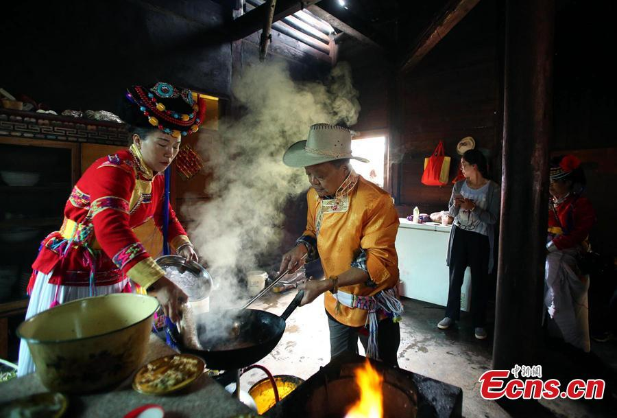 Sichuan cuisine master Fu Zuming (R) teaches cooking skills to a woman in a family of Mosuo people next to Lugu Lake in Yanyuan County, Southwest China's Sichuan Province, Sept. 13, 2018. Fu started learning to cook Sichuan food in his teens. During his visit to the Mosuo family, he combined the local specialties with Sichuan cuisine techniques to make a new dish. (Photo: China News Service/Wang Lei)