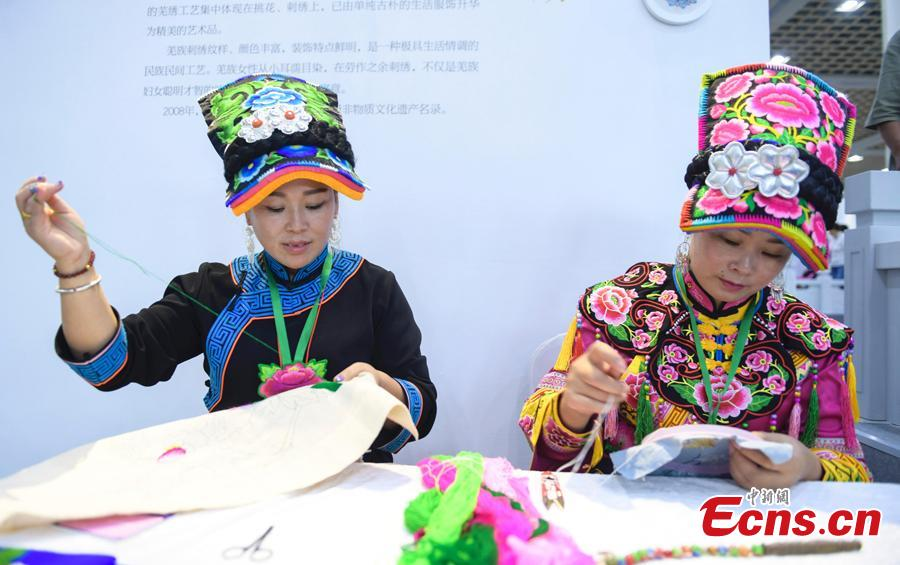 Two female embroiderers show their skill at the fifth China Intangible Cultural Heritage Expo in Jinan City, Shandong Province, Sept. 13, 2018. The expo was jointly organized by the Ministry of Culture and Tourism and the Shandong provincial government. More than 200 practitioners of traditional arts and craftsmanship will showcase their skills at the expo, which will include stilt-walking, embroidery by the Qiang people and straw-weaving craftworks. (Photo: China News Service/Zhang Yong)