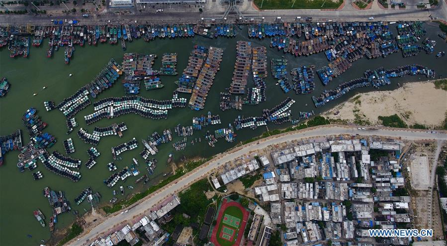 Aerial photo taken on Sept. 14, 2018 shows fishing boats returning to harbor at a fishing port in Sanya, south China\'s Hainan Province. Mangkhut, the 22nd typhoon this year, is expected to land in south China\'s Guangdong and Hainan provinces on the night of Sept. 16. (Xinhua/Yang Guanyu)