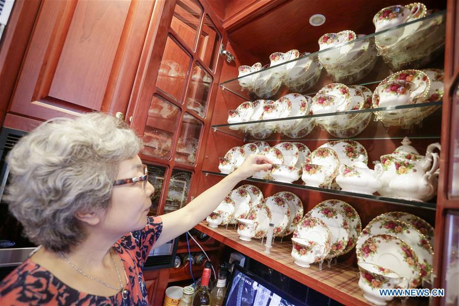 Teacup collector June Gao displays her collections inside her house in Vancouver, Canada, Sept. 13, 2018. (Xinhua/Liang Sen)