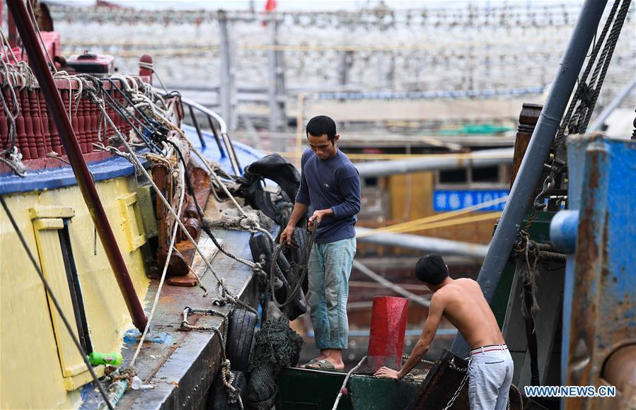 Fishermen fix fishing boats at a fishing port in Sanya, south China\'s Hainan Province, Sept. 14, 2018. Mangkhut, the 22nd typhoon this year, is expected to land in south China\'s Guangdong and Hainan provinces on the night of Sept. 16. (Xinhua/Yang Guanyu)