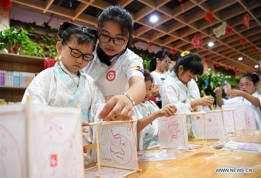Children make lanterns to greet the upcoming Mid-Autumn Festival at a community in Hefei, capital of east China\'s Anhui Province, Sept. 15, 2018. (Xinhua/Liu Junxi)
