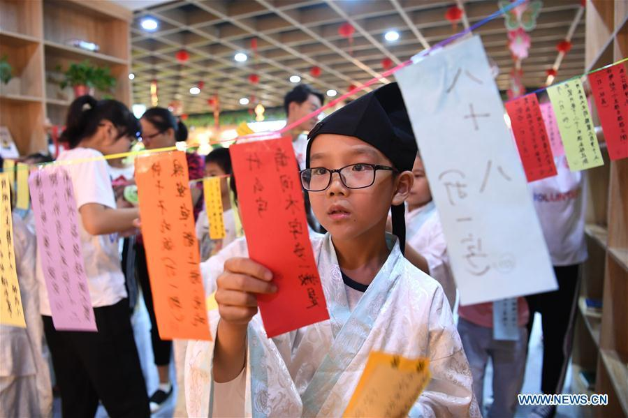 A child takes part in a lantern-riddle activity to greet the upcoming Mid-Autumn Festival at a community in Hefei, capital of east China\'s Anhui Province, Sept. 15, 2018. (Xinhua/Liu Junxi)