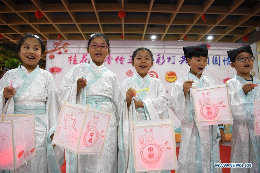 Children show lanterns they made to greet the upcoming Mid-Autumn Festival at a community in Hefei, capital of east China\'s Anhui Province, Sept. 15, 2018. (Xinhua/Liu Junxi)