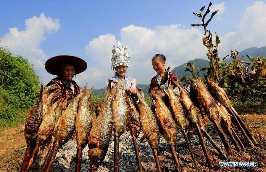 Villagers roast fishes during harvest celebrations held at a village of Miao ethnic group in Gandong Township in Miao Autonomous County of Rongshui, south China\'s Guangxi Zhuang Autonomous Region, Sept. 15, 2018. (Xinhua/Long Tao)