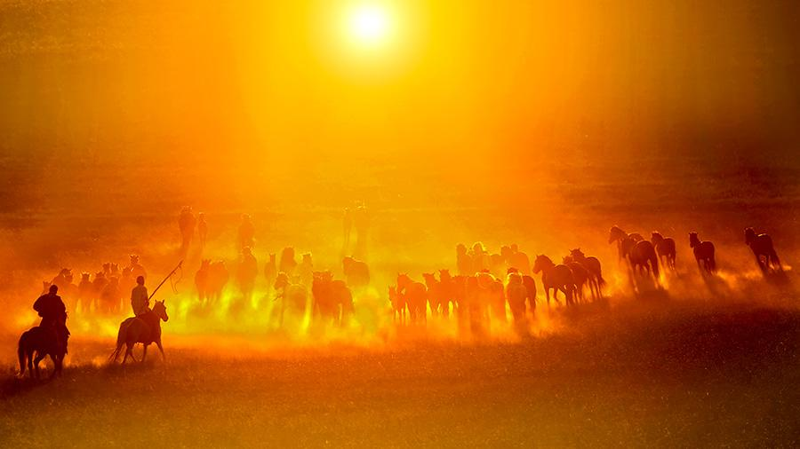 Autumn brings beautiful sunsets over open grasslands at Xilin Gol league in the Inner Mongolia autonomous region. Bathing in the sunset glow, working horses and herdsmen create a picturesque setting. (Photo/China Daily)