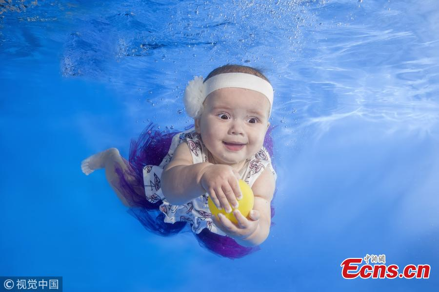 A baby girl swims underwater in a pool in Odessa, Ukraine. (Photo/VCG)