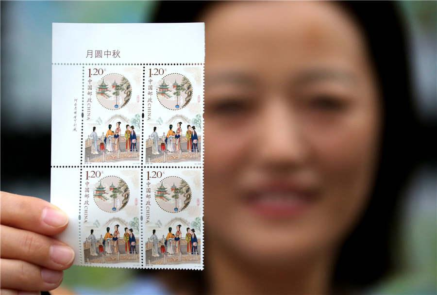 A stamp collector shows the newly issued stamp themed on the Mid-Autumn Festival, in Zaozhuang city, Shandong Province, Sept. 15, 2018. (Photo/Asianewsphoto)